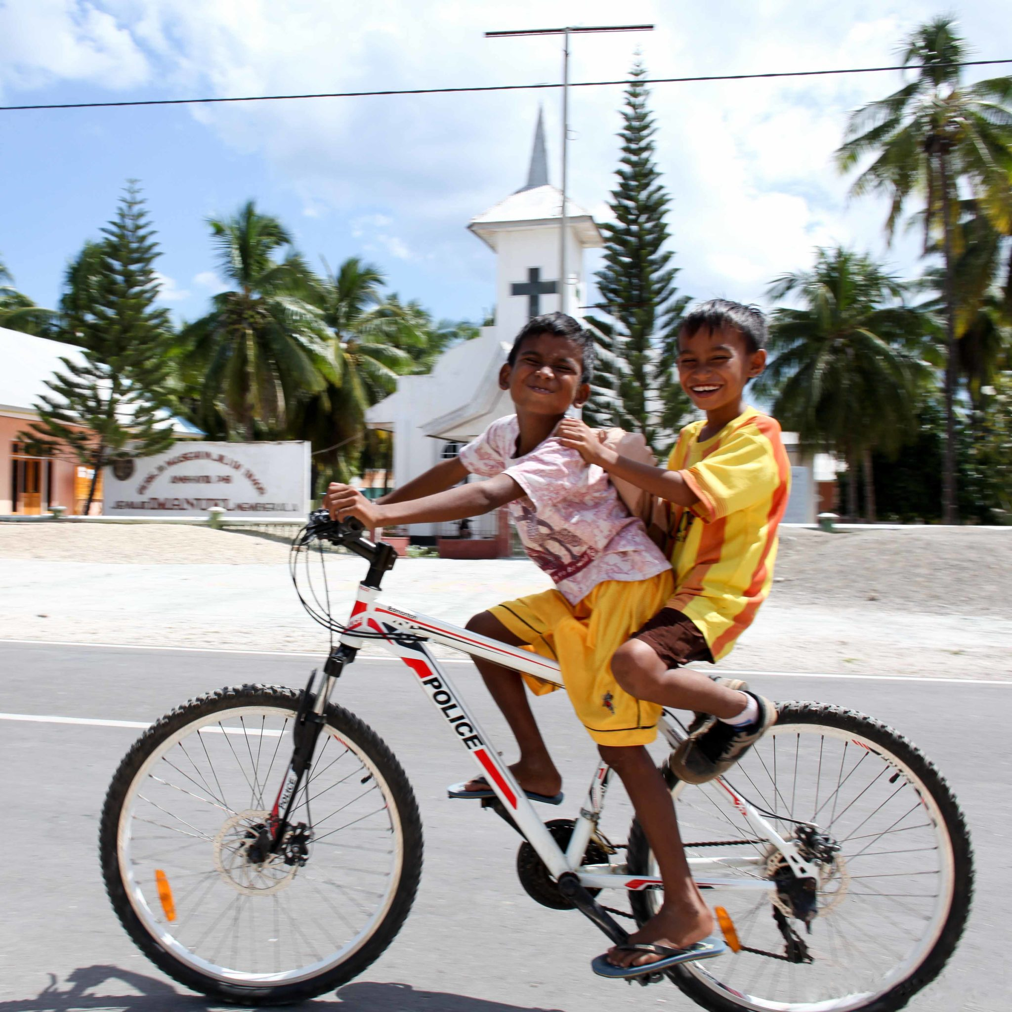 two young boys bycicle church nemberala rote island indonesia anugerah